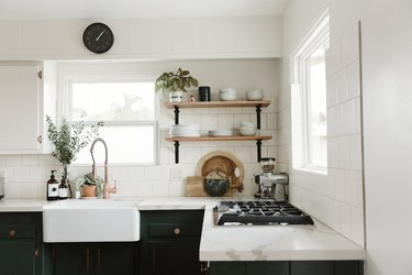 apron-front white cast iron sink inset in black cabinetry beneath exposed  shelving