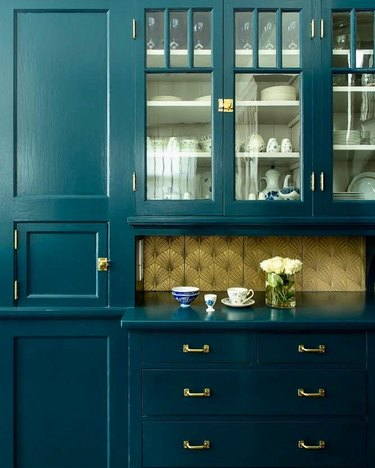 Gold art deco backsplash with leaf design alongside teal cabinets
