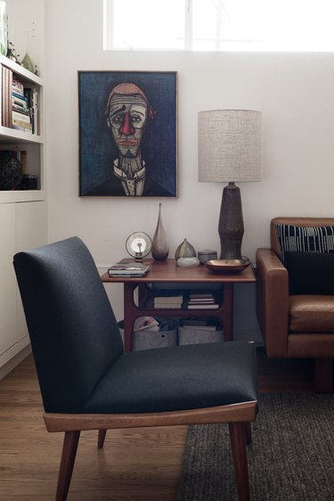 midcentury modern family room with armless sitting chair, coffee leather couch, and abstract clown painting.