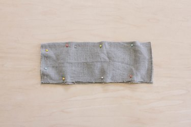 Two gray linen fabric pieces pinned together with right sides facing in