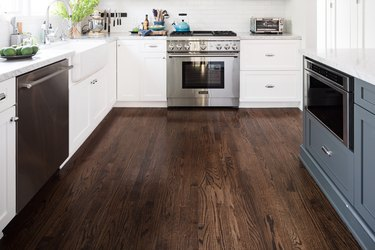 Dark wood floors in kitchen with blue and white cabinets