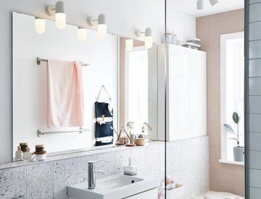 coastal bathroom lighting idea with wall sconces in pink and white space