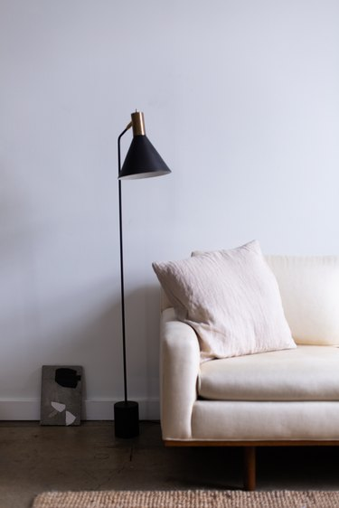 white couch in midcentury modern family room with black and gold metal standing lamp.