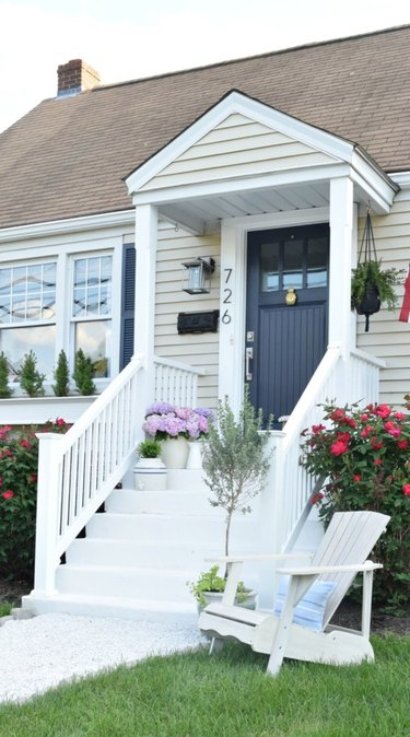Cream Craftsman home exterior with navy blue front door and white front steps