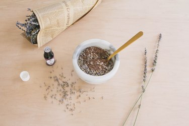 Mixing flax seeds, dried lavender and essential oil in marble bowl