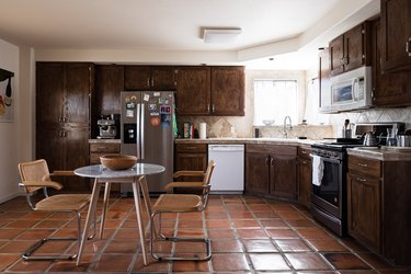 Tile floors in kitchen with brown cabinets