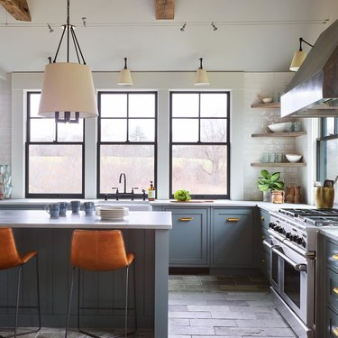 Blue and gray kitchen with leather bar stools and slate floor