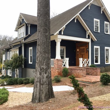 Dark navy blue Craftsman home exterior with white trim and warm wood front door