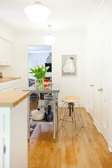 narrow stainless steel kitchen island in room with wood floors and white cabinets