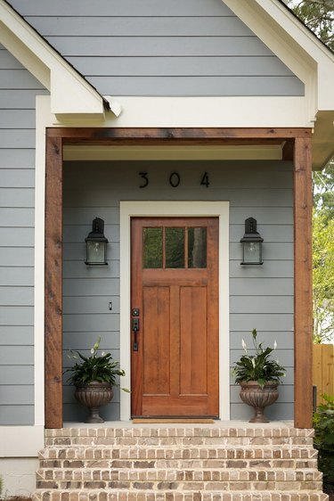 Blue gray Craftsman home exterior with warm wood front door and posts