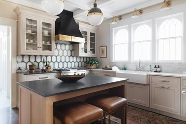 art deco backsplash with beige cabinets and farmhouse sink