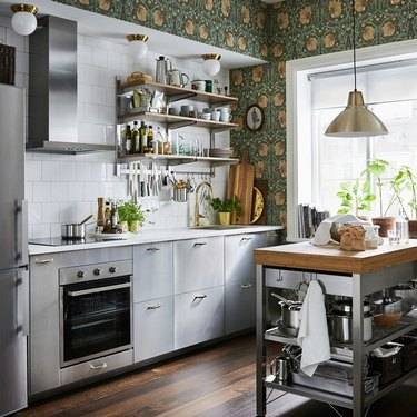 stainless steel kitchen island with wood butcher block counter in kitchen with wallpaper