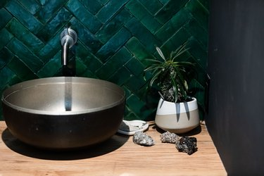 bowl sink with chevron dark green tile wall and wall-mounted faucet