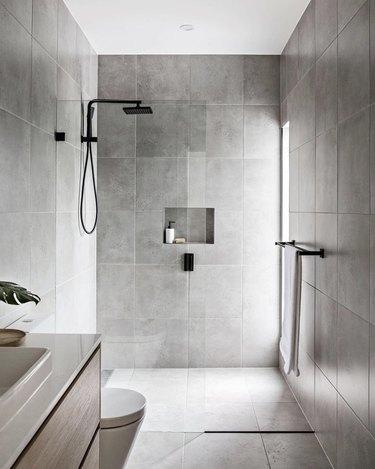 Gray tiled minimalist bathrooms with matte black fixtures