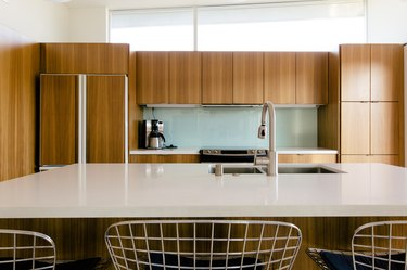 kitchen with wood paneled cabinets, white countertops and kitchen island with a sink