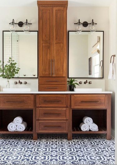 rustic bathroom lighting idea with double bulb clear glass sconces above mirrors