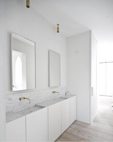 White minimalist bathrooms with brass fixtures