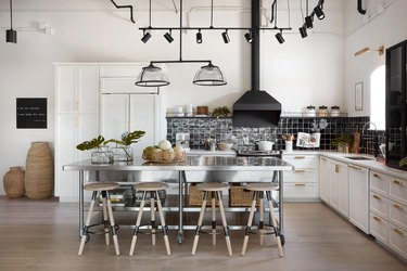 stainless steel kitchen island with wicker baskets and barstools