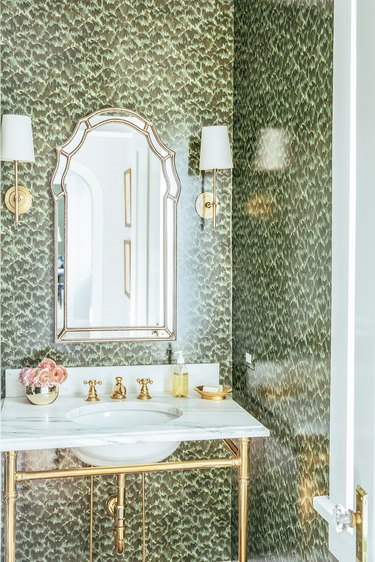 hollywood regency bathroom with brass details and green wallpaper