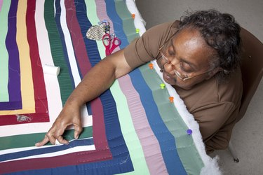 woman working on Gee's Bend style quilt