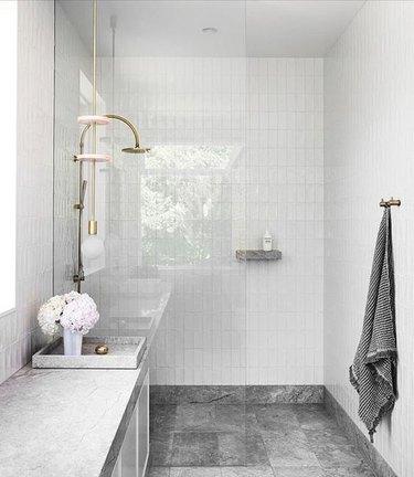 natural limestone vanity top and dark stone tiles in stone tile bathroom