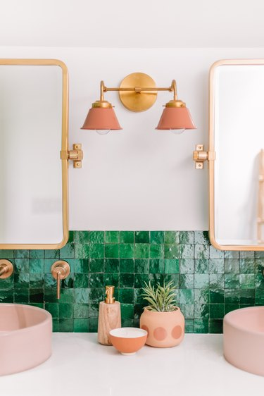pink and brass bathroom wall lighting idea with double wall sconce