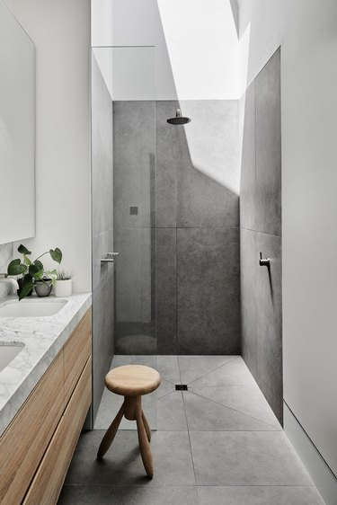 stone tile bathroom with Carrara marble and wood details