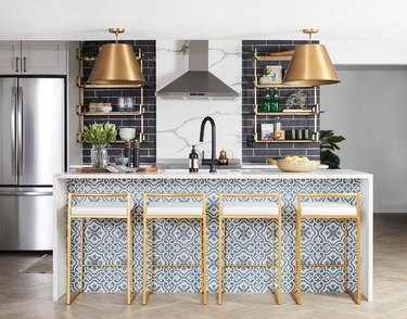 patterned blue kitchen island with white waterfall countertop and brass stools