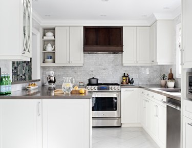 White kitchen with marble white kitchen floor tiles and wooden hood