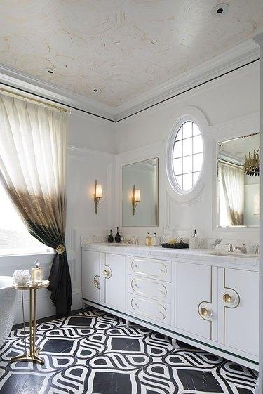 hollywood regency bathroom with black and white floor tile