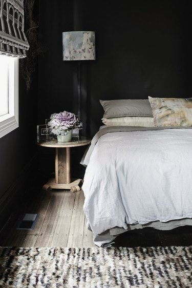black bedroom with light furnishings