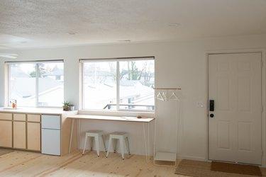 simple minimalist living space with cabinet, large windows, wood floor