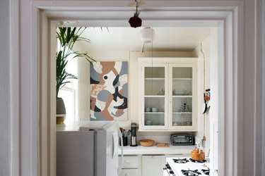 small kitchen with glass-faced kitchen countertops, a stove and abstract art on the wall