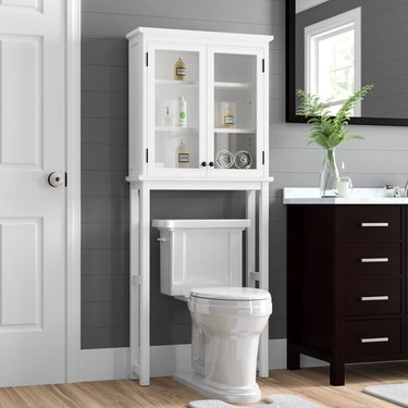 over the toilet bathroom cabinet with glass paneled doors