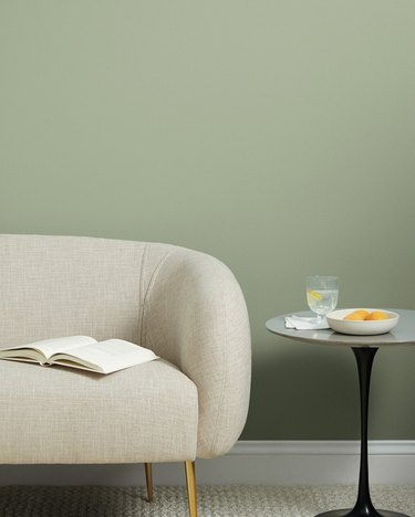 beige couch with table nearby and green wall