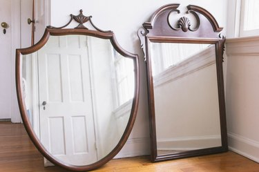 Two dark wood thrift store mirrors leaned against wall