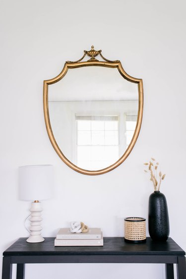 DIY gold gilt mirror hanging on wall above black table with lamp, books and vase