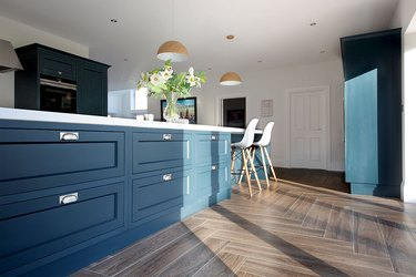 kitchen space with blue cabinets and dark porcelain tile in dark hardwood style