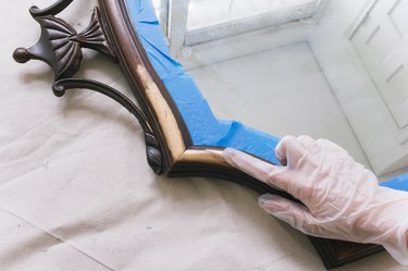 Rubbing gilding wax onto wooden mirror frame with latex glove