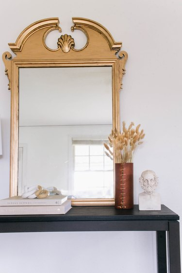 DIY antique gilt mirror leaned against wall on black table with books, vase and bust
