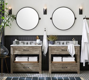 bathroom space with tiled floor, two wood vanities, two round mirrors, and three light sconces
