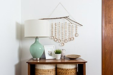 Wood wall hanging over console table and mint green lamp