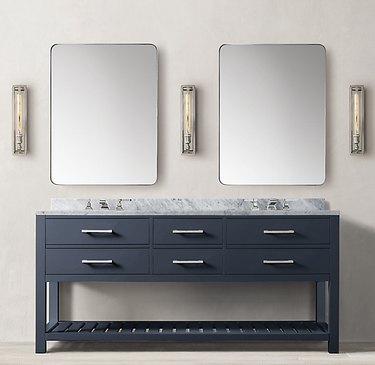 navy bathroom double vanity with two rectangular mirrors and three light sconces