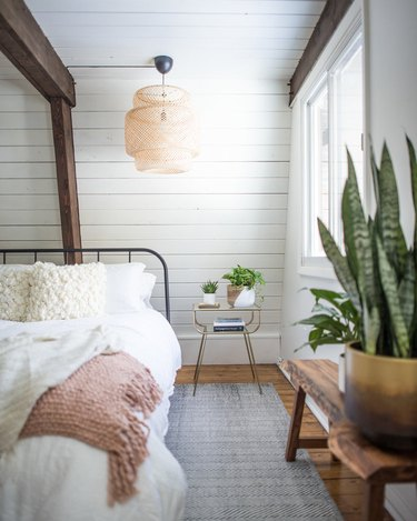 rustic bedroom lighting idea with IKEA rattan pendant light hanging from ceiling with shiplap walls