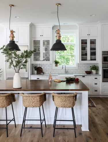white farmhouse kitchen with black industrial pendant lights above island