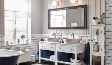 bathroom space with white tiling and two white bathroom vanities, mirror, and two light sconces above