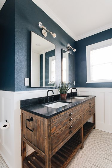 bathroom space with white and blue walls with wood bathroom vanity with black countertop
