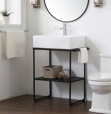 bathroom vanity with white sink and black legs near while toilet