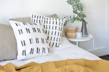 Mudcloth pillows on bed with mustard yellow blanket