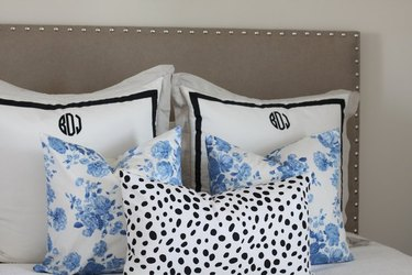 Padded headboard with black, white, and blue pillows